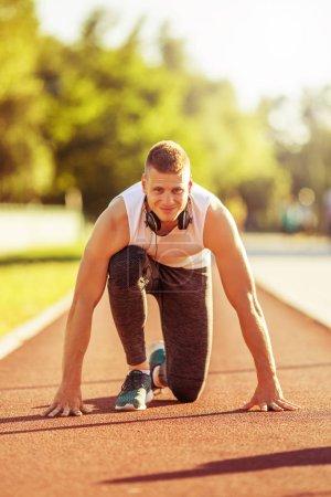 Photo pour Jeune homme en position de départ pour courir sur la piste. L'image est intentionnellement tonique . - image libre de droit