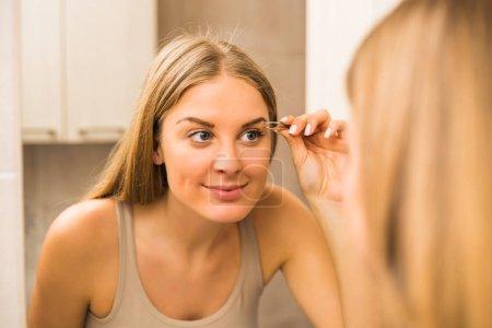 Photo pour Belle femme, épilation des sourcils dans salle de bain. - image libre de droit