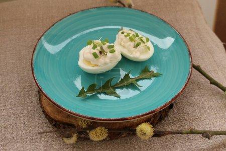 Photo pour Œufs durs avec mayonnaise et herbes et une feuille de pissenlit sur une assiette turquoise, le fond est un tissu de lin auto-tissé et une branche de saule en fleurs. Le printemps. Rapide et savoureux. Manger à la maison . - image libre de droit