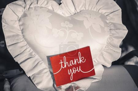 Photo for Postcard with the inscription Thank you on a red background on a white pillow in the form of a heart. - Royalty Free Image