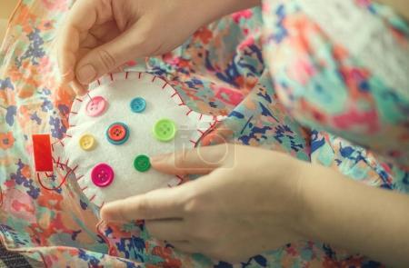 Foto de Mujer manos cosen corazón de algodón blanco con diferentes colores de botones. Hecho a mano el concepto del amor. Día de San Valentín. - Imagen libre de derechos