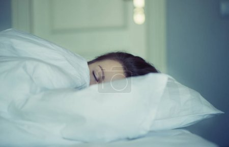 Photo for A girl lies in bed can't fall asleep thinking and dreaming. Insomnia. Psychology - Royalty Free Image