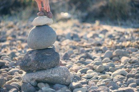Photo pour Pyramide de pierres sur la plage contre la mer, le coucher du soleil - image libre de droit