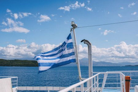 Photo for The Greek flag on the ship against the background of the sea of islands and opposite the ships. Sea voyage in the Ionian sea. - Royalty Free Image