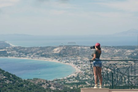 Female photographer in a red cap with a camera stands on the balcony opposite of the Greek city of Volos at sunset. Volos Greece. View from the mountain on the Volos