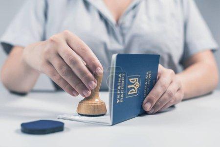 Photo pour Immigration et contrôle des passeports à l'aéroport. femme agent de contrôle des frontières met un timbre dans le passeport ukrainien. Concept - image libre de droit