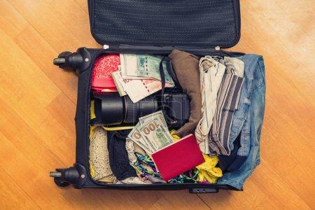 Photo pour Une valise avec des choses et un passeport étranger. De l'argent asiatique et des billets de cent dollars pour voyager. Concept - image libre de droit