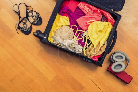 Photo pour Une valise pleine de maillots de bain par terre. Concept de voyage - image libre de droit