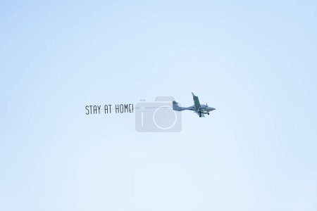Photo for Airplane with STAY HOME text or message to citizens (people) of the country and the world flying in the blue sky. protect from chinese Coronavirus or Covid-19 epidemic. Quarantine. - Royalty Free Image