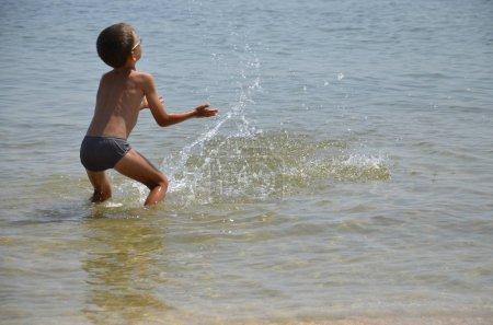 Ein kleiner, glücklicher Junge steht im Wasser und plätschert. Ein fröhliches Kind springt an die Küste, an den Strand. Das Kind genießt das Meer und planscht mit Quark im Wasser. Rückansicht.