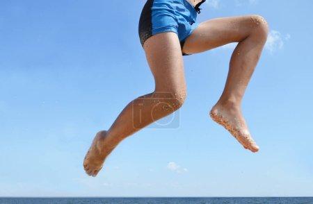 Photo pour Le jeune homme heureux sauta contre le ciel bleu par la mer. Joyeuse adolescente dans un saut. Vacances au bord de la mer. Les pieds du jeune garçon rebondirent sur le bord de la mer . - image libre de droit