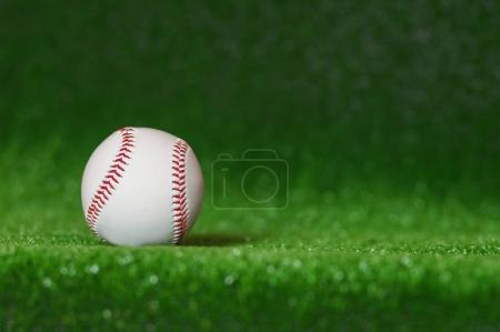 a baseball in a grass background