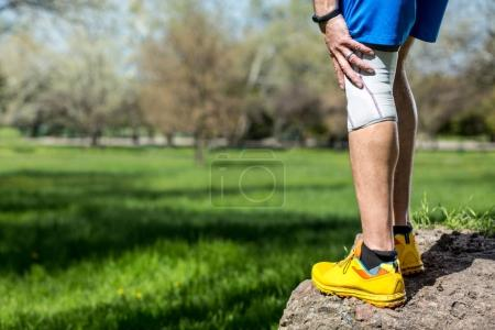 Male runner knee pain with bandage