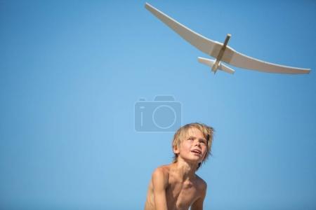 Boy with plane over blue sky