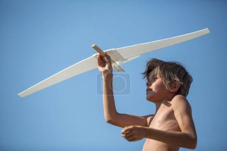 Boy with plane over blue sky