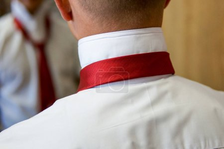Man fixing red tie on white shirt.