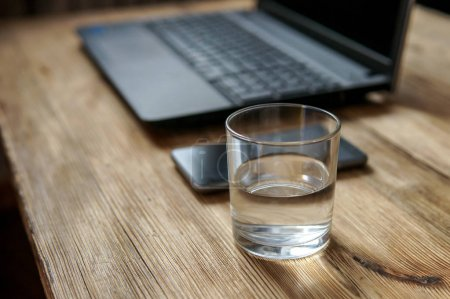 Working process - image of smartphone,  glass of water, lap top . selective focus on glass of water