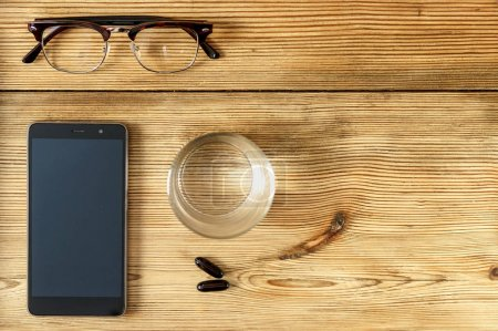 Modern male accessories smarphone, glasses and health care pill with glasse of water