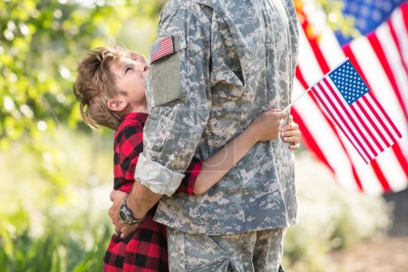 Happy reunion of soldier with family, son hugging his father