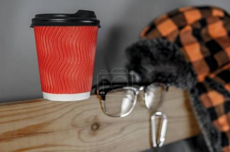 Travel accessories set on wooden shelf and gray background, focus on cup of coffee