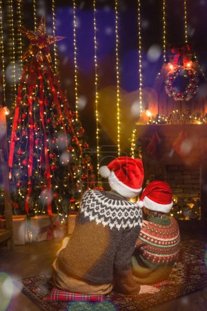 Photo for Family on Christmas eve at fireplace. Kids opening Xmas presents - Royalty Free Image