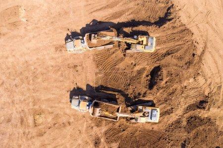 Photo pour Image aérienne d'un vaste site d'excavation avec plusieurs véhicules de l'industrie lourde travaillant, tels que des excavatrices, des camions de transport articulé et plus encore. - image libre de droit