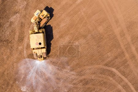 Photo for Aerial image of a Vast excavation site with multiple heavy industry vehicles working, such as Excavators, Articulated hauler trucks and more. - Royalty Free Image