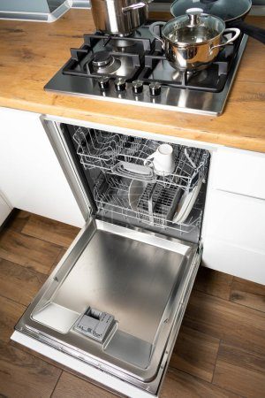 High angle view of open dishwasher in modern kitch...