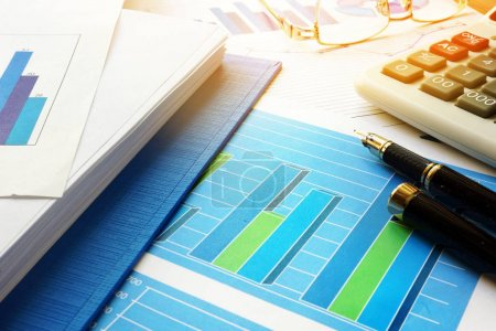 Business analysis and accounting concept. Office table with pile of financial documents.