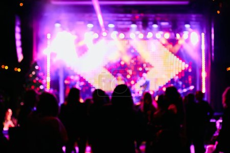 Photo for Crowd up in front of bright stage. Blurred background - Royalty Free Image