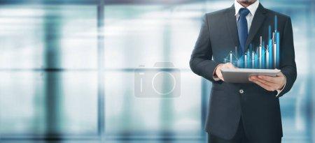 Photo pour Croissance des graphiques de plan d'homme d'affaires et augmentation des indicateurs positifs de graphique dans son entreprise, tablette en main - image libre de droit