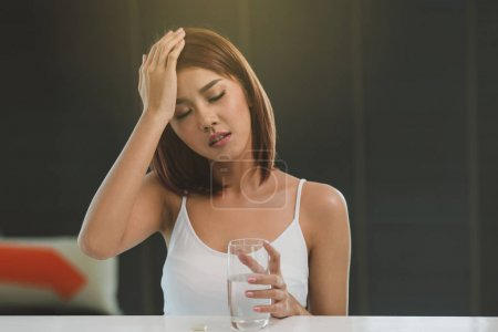 Photo pour Pilule prise de belle jeune femme asiatique contre les maux de tête à la maison. (Photo soft) - image libre de droit