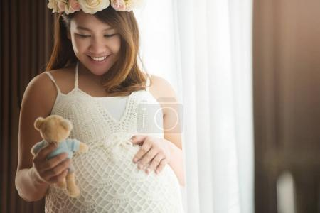 pregnant woman holding a teddy bear doll
