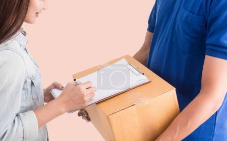 Delivery man giving a cardboard box to young woman
