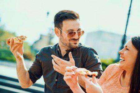 Photo pour Portrait d'un couple heureux. Ils sont rire et manger des pizzas et avoir un grand temps - image libre de droit