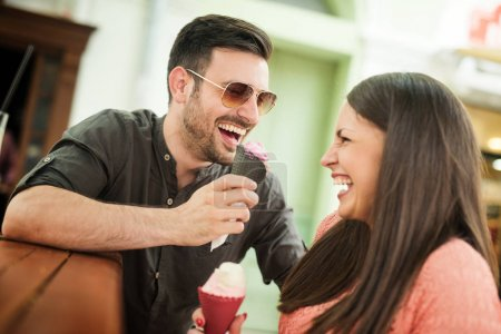 Young couple eating ice-cream in the city