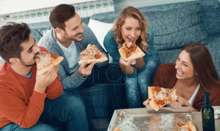Photo for Friends eating pizza.They are having party at home, eating pizza and having fun. - Royalty Free Image