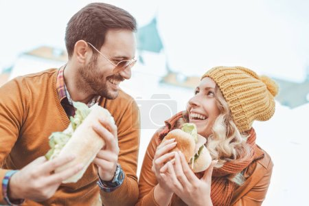 Photo for Young happy couple eating together outdoors. - Royalty Free Image