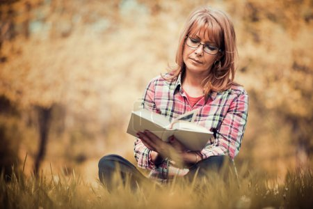 Photo for Portrait of beautiful woman reading book in nature. - Royalty Free Image