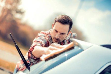 Photo pour Travailleur homme polissage voiture sur un lavage de voiture à l'extérieur. - image libre de droit