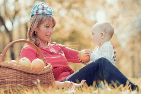 Photo pour Âgé de moyen belle mère et son petit fils adorable, avoir un pique-nique dans le parc ensoleillé - image libre de droit