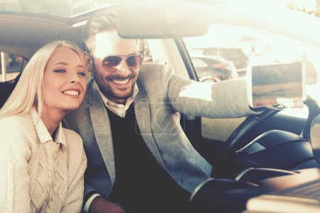 Photo for Happy young woman and a young man are laughing in the car,taking selfie. - Royalty Free Image