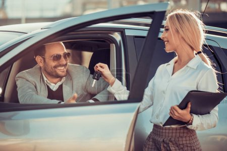 Young man receiving car key from saleswoman