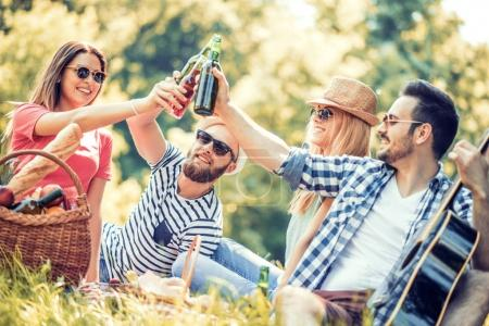 Photo pour Heureux jeunes amis ayant pique-nique dans le parc. Ils sont tous heureux, s'amuser, sourire et jouer de la guitare - image libre de droit