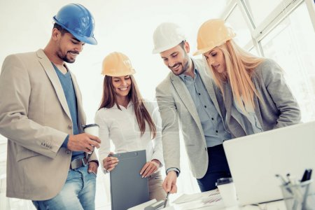 Construction workers checking the architectural plans