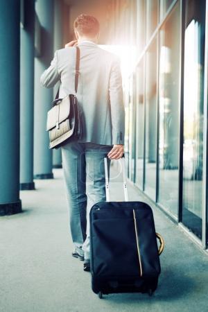 Elegant businessman walking with suitcase