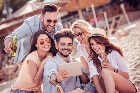 Group of cheerful friends taking selfie together with smart phone on beach.