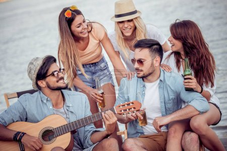 Friends enjoying singing together and playing guitar on the beach.They are all happy,having fun,smiling and playing guitar.