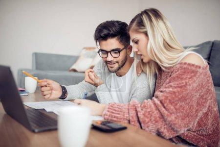 Photo pour Photo d'un couple adulte aimant utilisant un ordinateur portable et analysant ses finances avec des documents. . - image libre de droit