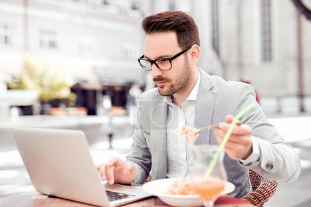 Businessman having a lunch break in cafe, he is eating fresh pasta.